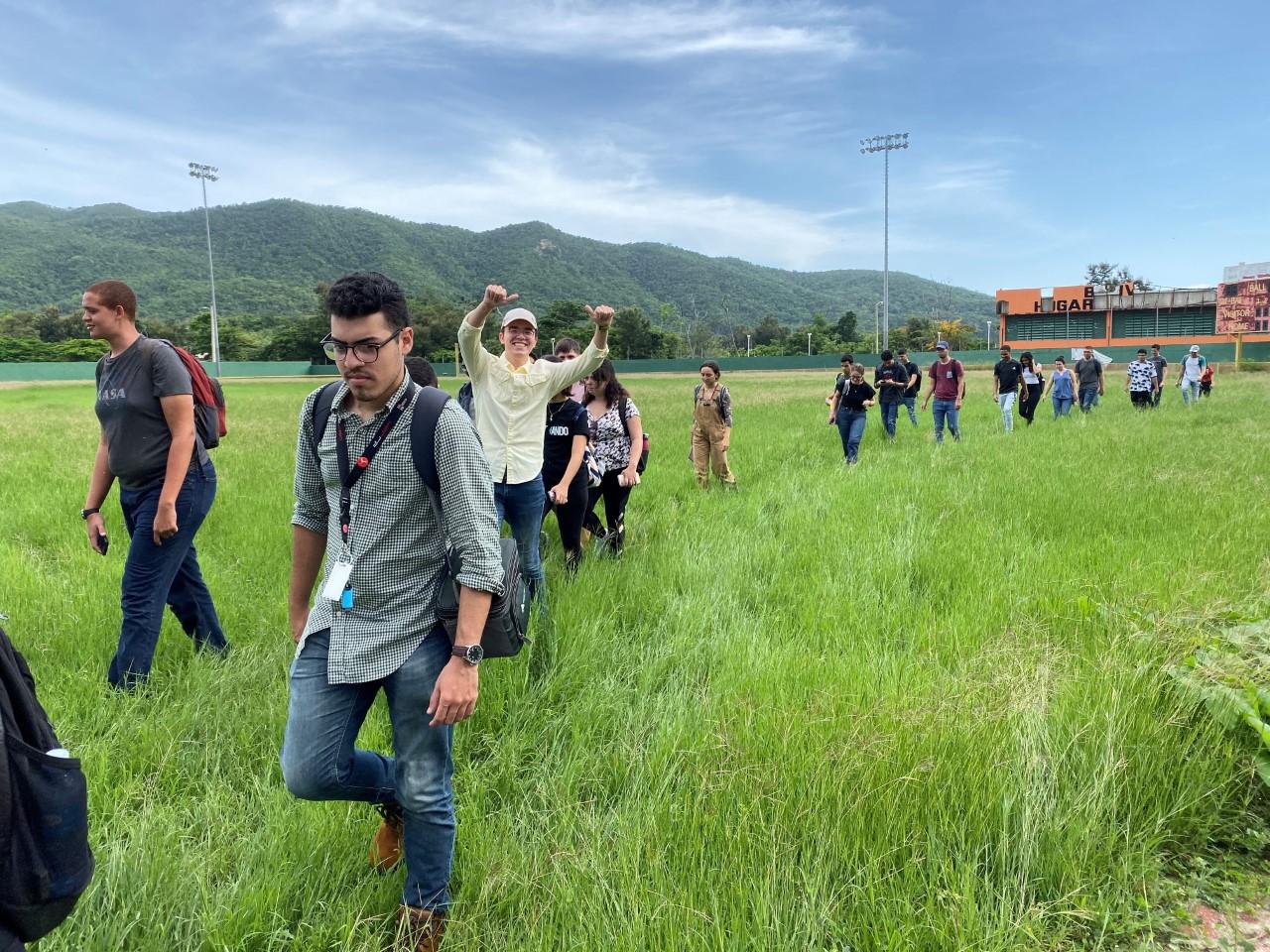 Students walking in a grass field